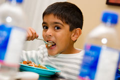 Take a big bite !. A child takes a big bite of his food stock photos