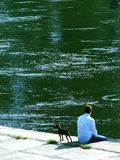 Take a break. Master and his dog are resting on the riverside Stock Photography