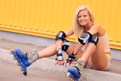 Take a break. Pretty young woman with roller skates Royalty Free Stock Photos