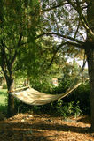 Take a break!. A hammock hangs in the shade of two trees Stock Images
