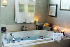 Take a break. A bathtub lit by candlelight with rose petals floating in the water royalty free stock photos
