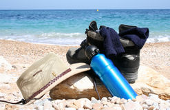 Take a break. Hiking boots, socks, hat and water bottle on a pebble beach Stock Photography