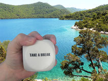 Take a break - Book your vacation. A hand holding the message Take a break. In the background you see the ocean with some islands Royalty Free Stock Photography