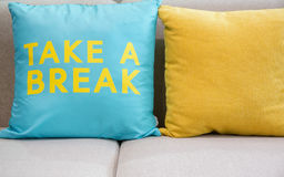 Take a break. Brown fabric sofa with big soft turquoise and yellow pillow saying take a break Royalty Free Stock Photography