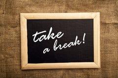 Take a break. Note on black message board stock photo