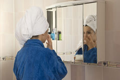 Take care of face skin. Woman in bathroom take care of her face skin,same series in Bathroom Royalty Free Stock Photo