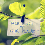 Take Care of our Planet. Concept with a handwritten note attached to a twig of fresh green sunlit leaves by a wooden clothes peg depicting the conservation of Royalty Free Stock Photo