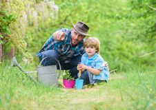 Take care of plants. Boy and father in nature with watering can. Gardening tools. Planting flowers. Dad teaching little stock photo