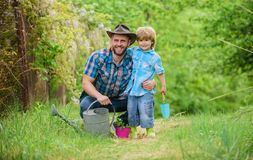 Take care of plants. Boy and father in nature with watering can. Spring garden. Dad teaching little son care plants. Little helper in garden. Planting flowers stock images