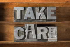 Take care tray. Take care phrase made from metallic letterpress type on wooden tray Stock Photos