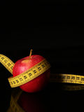 Take care of your body. An apple with a measuring tape around as a concept of good food good healt Stock Photos