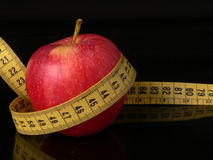 Take care of your body. An apple with a measuring tape around as a concept of good food good healt Stock Images