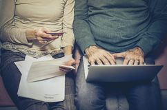 Take care of your finances in old days. Senior couple at home checking finance on credit card. Close up stock images
