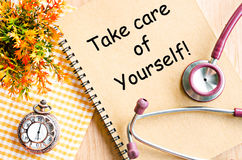 Take care of yourself. Take care of yourself on diary book and stethoscope with pocket watch on table royalty free stock photo
