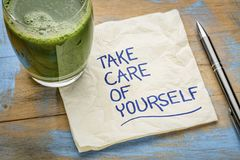 Take care of yourself - napkin concept. Take care of yourself - inspirational handwriting on a napkin with a glass of green juice stock photo