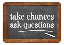 Take chances, ask questions. Motivational advice on a vintage slate blackboard Stock Image
