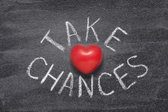 Take chances heart. Take chances phrase handwritten on chalkboard with red heart symbol instead of O Royalty Free Stock Images