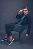 Take a closer look at my style. Confident young handsome man adjusting his glasses and looking at camera while sitting in chair against grey background royalty free stock photo