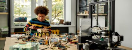 Free Take Control. Boy Using Screwdriver While Fixing Bolts On A Robot Vehicle. Smart Kids And STEM Education. Stock Image - 174458061