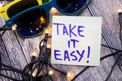 Take it easy A handwritten motivational quote. positive attitude words on the wooden background with two sunglasses of various col. Take it easy handwritten stock image