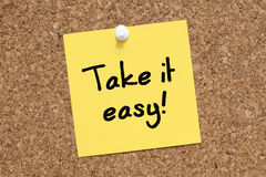 Take it Easy. Note pinned on cork noticeboard Royalty Free Stock Image