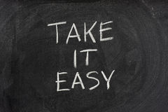 Take it easy phrase on blackboard. Take it easy phrase handwritten with white chalk on blackboard Stock Photo