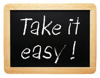 Take it easy sign. Take is easy sign written on blackboard or chalkboard, white background royalty free stock photo