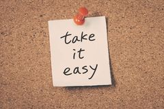 Take it easy. Reminder message on a cork board Stock Images