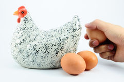 Take Egg from White Ceramic Hen.  royalty free stock images