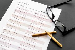 Take the exam. Exam sheet near glasses and pencil on black background.  royalty free stock images