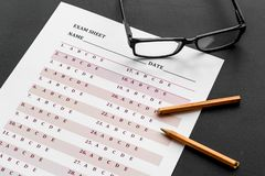 Take the exam. Exam sheet near glasses and pencil on black background.  stock photography