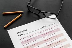 Take the exam. Exam sheet near glasses and pencil on black background.  royalty free stock photography