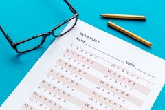 Take the exam. Exam sheet near glasses and pencil on blue background.  royalty free stock photos