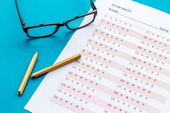 Take the exam. Exam sheet near glasses and pencil on blue background.  stock images
