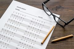 Take the exam. Exam sheet near glasses and pencil on dark wooden background.  royalty free stock photos