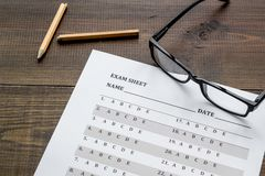 Take the exam. Exam sheet near glasses and pencil on dark wooden background.  stock photography