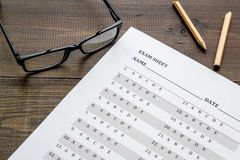 Take the exam. Exam sheet near glasses and pencil on dark wooden background.  royalty free stock image
