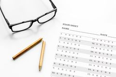 Take the exam. Exam sheet near glasses and pencil on white background.  stock photo