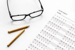 Take the exam. Exam sheet near glasses and pencil on white background.  stock photos
