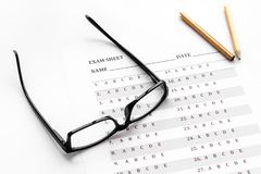 Take the exam. Exam sheet near glasses and pencil on white background.  royalty free stock images