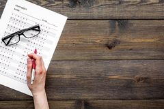 Take the exam, write the exam. Hand holding pen near exam paper on dark wooden background top view copy space Stock Images