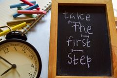 Take the first step phrase colorful handwritten on chalkboard, alarm clock with motivation and education concepts. royalty free stock photo
