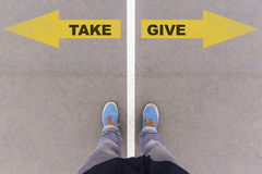 Take or give text arrows on asphalt ground, feet and shoes on fl Royalty Free Stock Image