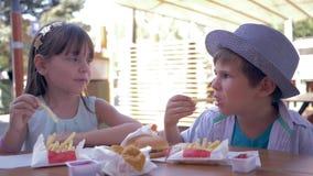 Take-$l*away τρόφιμα, ευτυχή παιδιά φίλων που τρώνε τις τηγανιτές πατάτες με τη σάλτσα και τα burgers στον καφέ οδών κατά τη διάρ φιλμ μικρού μήκους