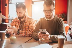 Take a look on beautiful and handsome bearded men sitting at te table and holding phones. They are looking only at their. Screens. Guys are busy. Close up Stock Photos