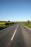 Take Me Home Country Road. A country road winds through the British countryside in Worcestershire. A yellow field edges the smooth tarmac road, providing a royalty free stock photo