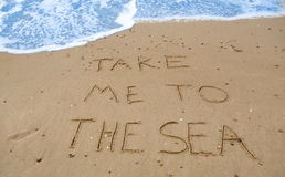 Take me to the sea. Written in the sand at the beach Royalty Free Stock Photo