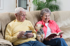 Take me For A Walk. A retired couple relaxing is interrupted by their little dog looking for attention Royalty Free Stock Images