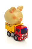 TAKE THE MONEY AND RUN. A piggy-bank is loaded on a toy-truck Royalty Free Stock Photos