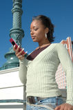 Take my Call. Beautiful Black woman standing outside in a city scene using her cell phone. Woman with expressions on her face as she uses her cell phone Stock Photography